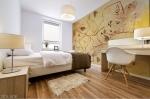 stampa murale con tema astratto con fili e forme geometriche triangolari,rettangolari con riccioli in tonalità di colore giallo su parete di camera da letto