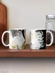 coppia di tazze classiche con design astratto dai colori fluidi con contrasti di bianco e nero e sfumature di giallo su mensola
